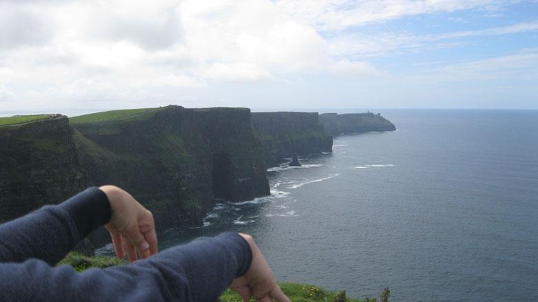 Foto: Cliffs of Moher. Man sieht meine Arme auf einer Mauer aufstützend und im Hintergrund die bekanntesten Steilklippen Irlands.