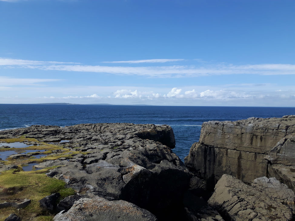Foto: Mini Cliffs of Moher. Berühmte Klippen Irlands. Das blitzblaue Meer ragt durch die Felswand hevor.
