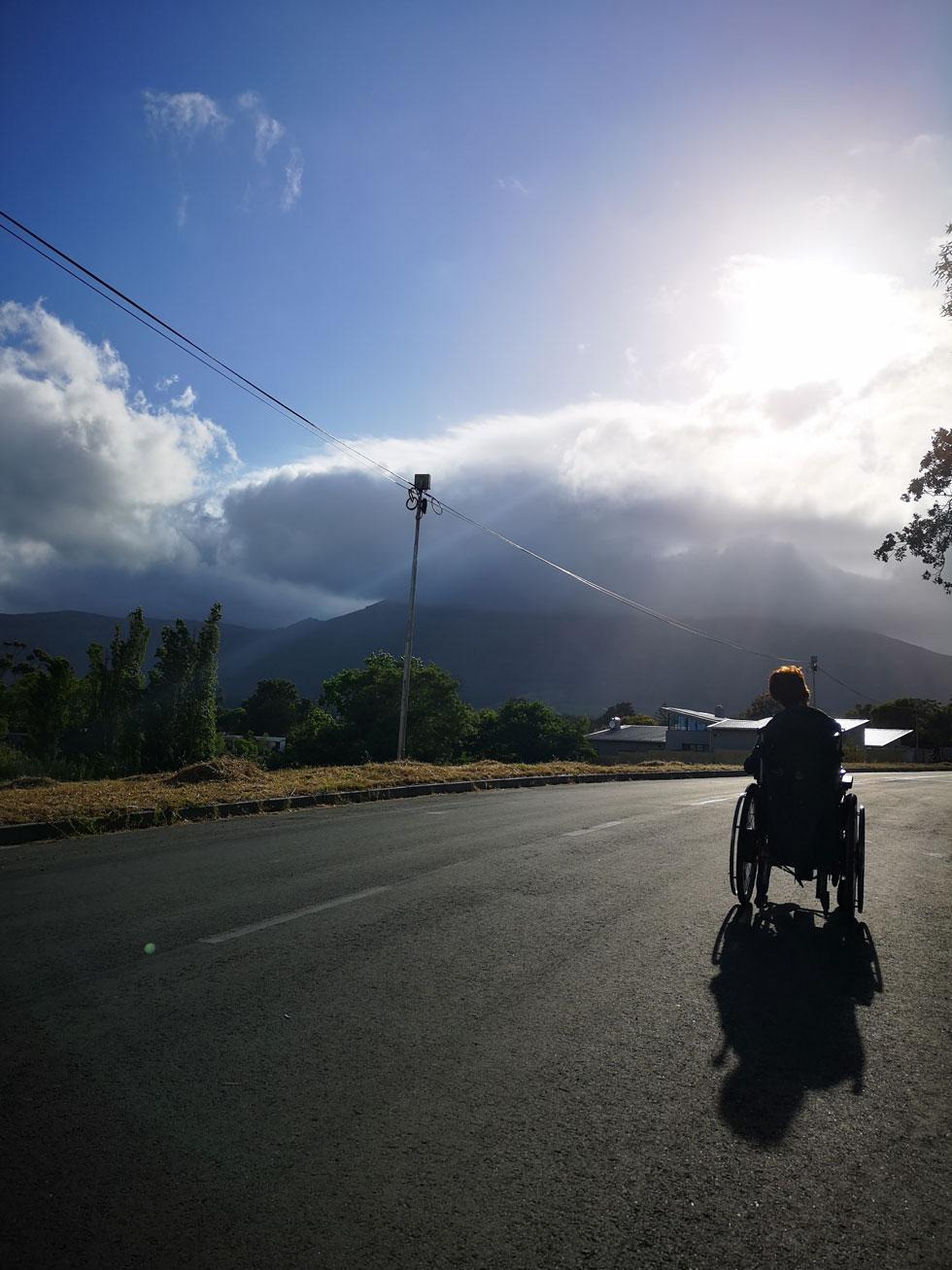 Foto: Kapstadt in der Abenddämmerung. Blick auf Berge, die von Wolken bedeckt werden. Sonne sticht hervor. Ich mit Rolli von hinten zu sehen.