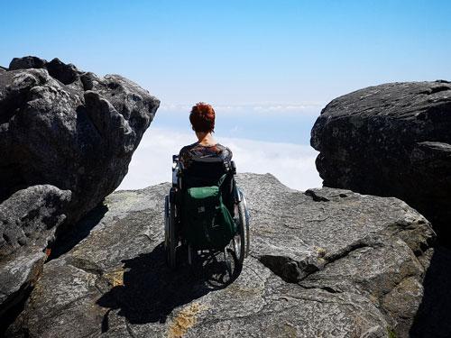 Foto: Man sieht mich von hinten. Ich sitze im Rollstuhl und stehe gerade am Abgrund des Table Mountains, in Kapstadt. Ich blicke auf eine Wolkendecke.