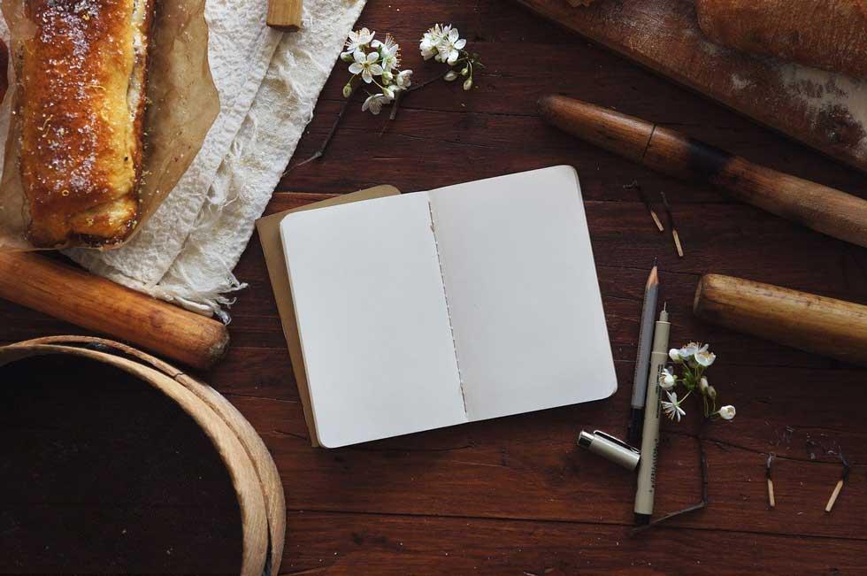 Foto: Tisch voller Schreibutensilien und Blüten, ein aufgeschlagenes, leeres Notizbuch und ein Strudel - falls man zwischendurch Hunger bekommt...