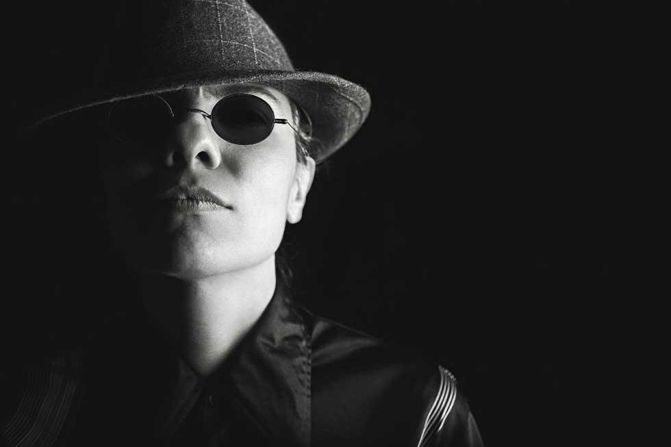 Schwarz-weiß-Foto: Frau Undercover mit Sonnenbrille und Hut