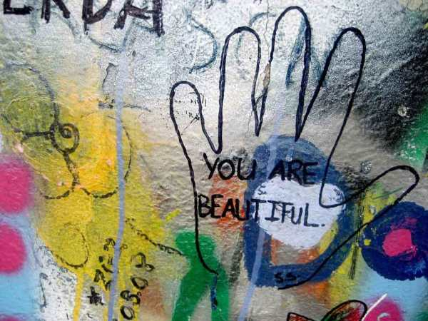 """Foto: Wandmalerei. Eine aufgemalte Hand mit der Inschrift """"You are beautiful""""."""