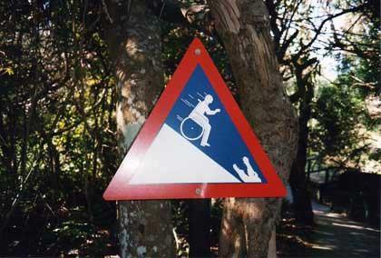 Foto: Verkehrsschild in Südafrika warnt Rollstuhlfahrer vor dem bergab fahren und unten ist ein Krokodil abgebildet